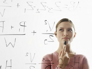 Young woman calculating equations on glass