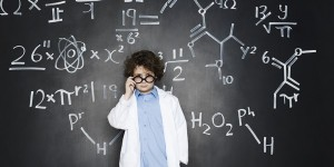 Boy as a professor with formulas behind him