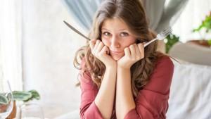 унылая девушка с вилкой и ножом