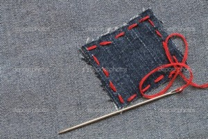 Needle and patch with red thread attached on jeans textured