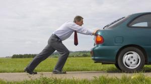 Geschaftsmann schiebt grunes Auto
